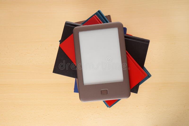 Ebook czytelnik na stosie książki zdjęcia stock