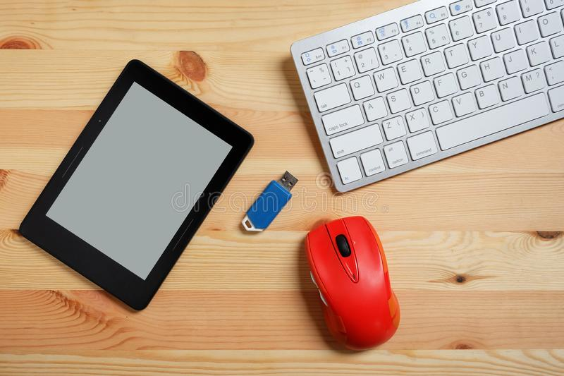 EBook czytelnik z pustego ekranu, klawiatury, myszy i b?ysku przeja?d?kami USB na drewnianej pod?odze, U?ywa? elektroniczny lub zdjęcie royalty free