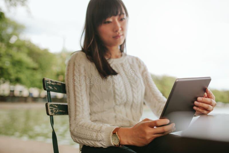 Ebook de la lectura de la mujer joven en su tableta digital fotografía de archivo libre de regalías