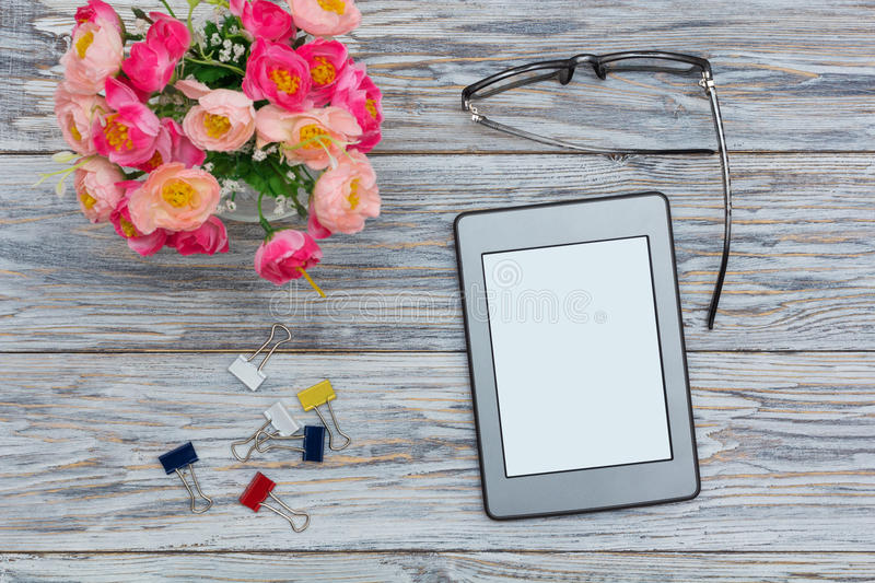 Ebook, flowers and glasses stock photos