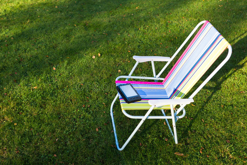 EBook-Leser auf dem Stuhl, Grashintergrund stockfoto