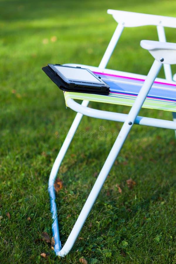 EBook-Leser auf dem Stuhl, Hintergrund des grünen Grases lizenzfreie stockfotografie