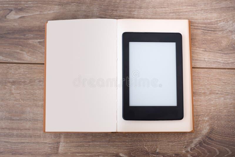 EBook-Leser auf einem Holztisch mit Buch lizenzfreies stockbild