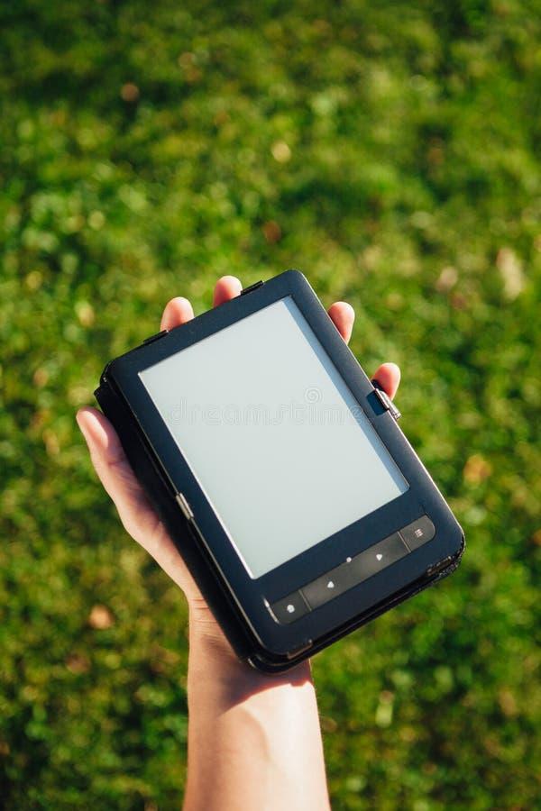 EBook-Leser in der Hand, Hintergrund des grünen Grases lizenzfreie stockfotos