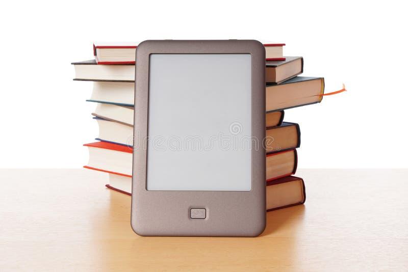 Ebook-Leser gegen Stapel von Büchern stockbilder