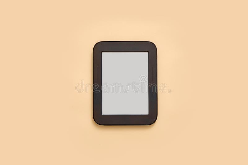 Ebook mockup with empty screen on beige background. Top view flat lay. Student or school library royalty free stock photography