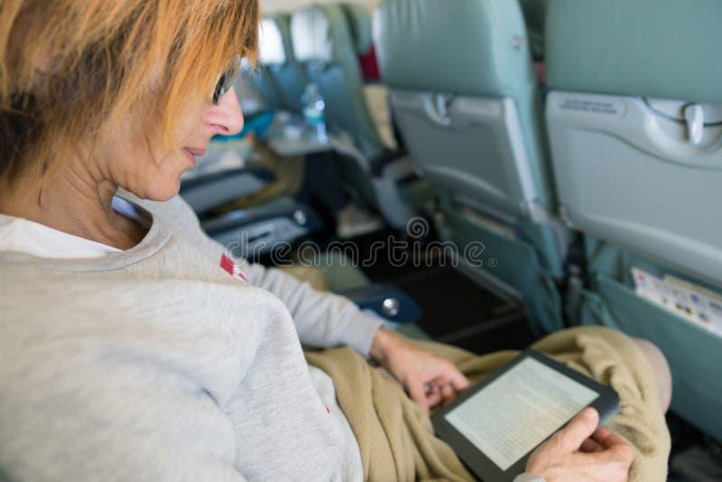 Ebook que senta-se dentro do avião, conceito da leitura da mulher da tecnologia das férias do curso fotos de stock royalty free