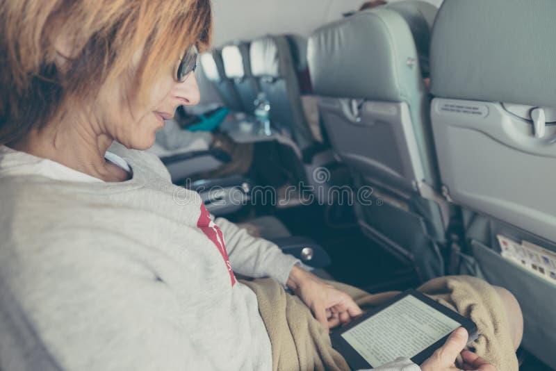 Ebook que senta-se dentro do avião, conceito da leitura da mulher da tecnologia das férias do curso fotos de stock