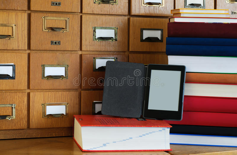 Ebook Reader in Front Library Catalogue - New Technology Concept. E-book reader in front library catalogue, next to a stack of books. New technology concept stock photography