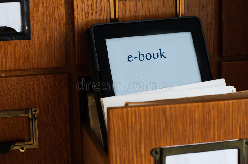 Ebook Reader in a Library - New Technology Concept. E-book reader in a library cards catalogue drawer. New technology concept stock images