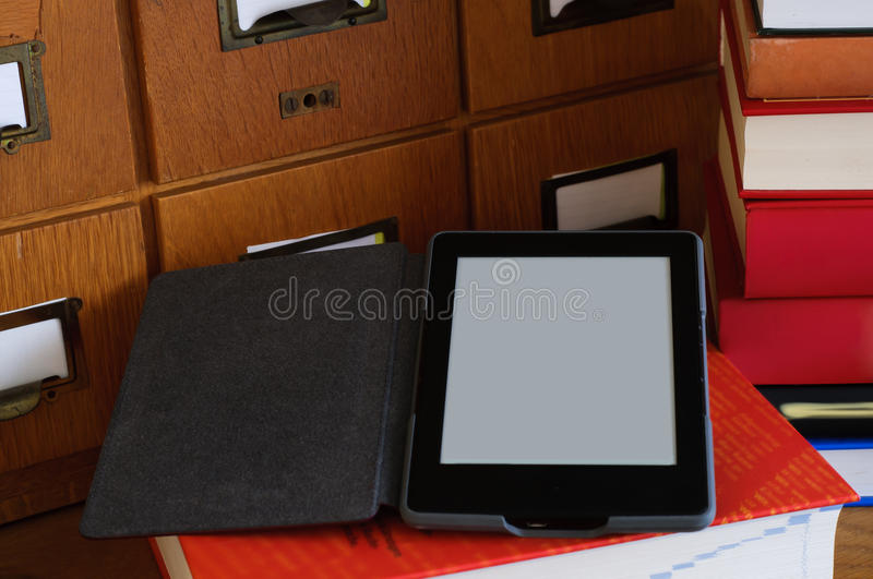 Ebook Reader in a Library - New Technology Concept. Ebook reader in a library next to a stack of books. New technology concept royalty free stock image