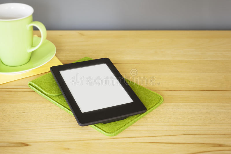 Ebook reader on a wooden table. An image of an ebook reader on a wooden table stock images