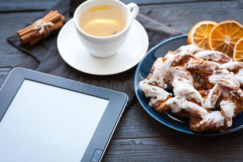 EBook und bayerischer Windbeutel mit zerquetschtem Haselnuss- und Zitronenfudge auf einer blauen Platte Im Hintergrund ein Schale stockfotografie