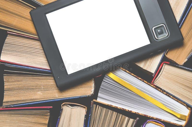EBooken med en vit skärm ligger på de öppna mång--färgade böckerna, som ligger på en mörk bakgrund, närbild arkivbild