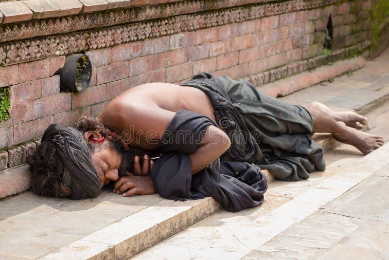 Żebrak Sadhu, święty mężczyzna uśpiony na chodniczku ulica w Kathmandu, Nepal zdjęcia stock