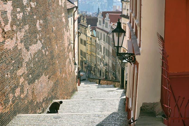 Żebraka klęczenie na schodkach prowadzi Praga kasztel w republika czech fotografia royalty free