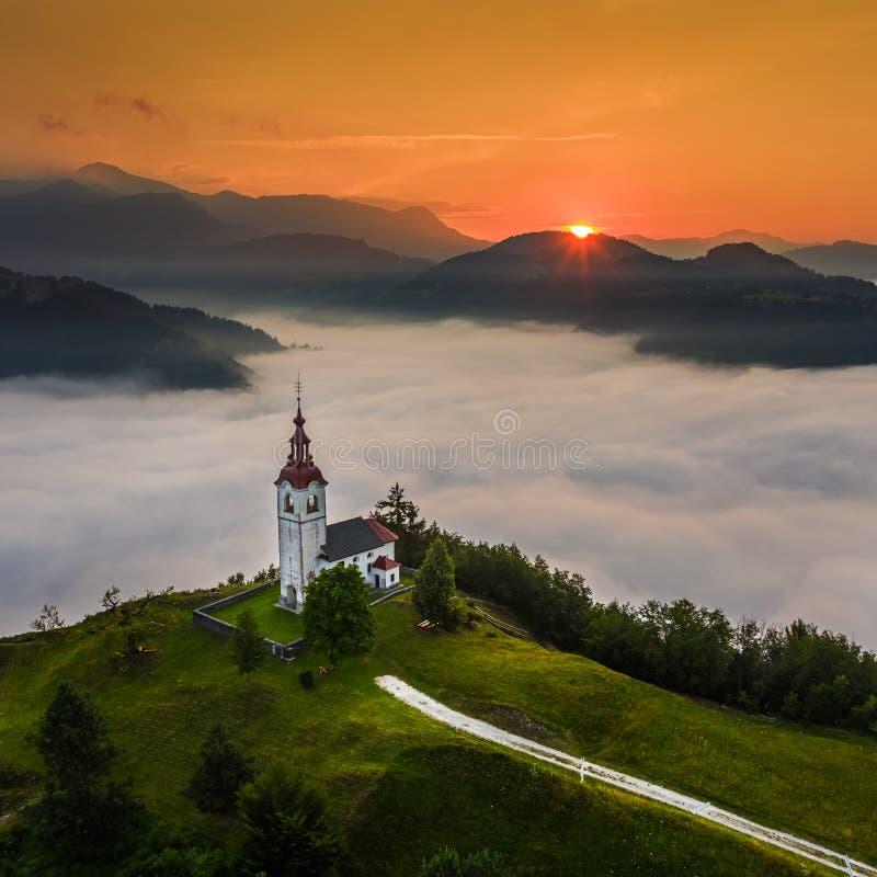 Free Šebrelje, Slovenia - Aerial Drone View Of The Beautiful Hilltop Church Of St.Ivan Sv. Ivan Cerkev At Sunrise With Morning Fog Stock Image - 207090381