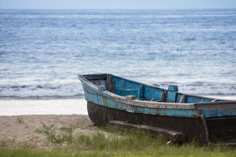 Ecuadorian Fishing Boat. A flat bottomed wooden fishing boat sits on the sandy shoreline awaiting its next voyage in Puerto Lopez Ecuador royalty free stock images