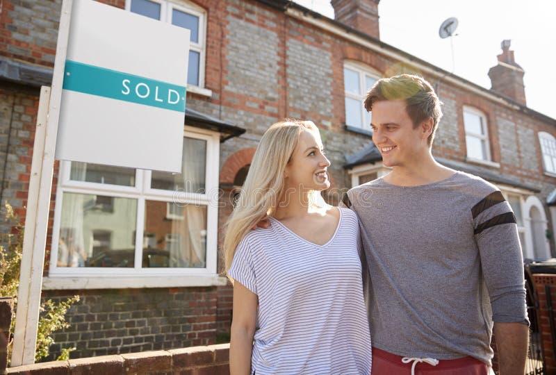 Eccitato coppia stare fuori di nuova casa con il segno venduto immagini stock libere da diritti
