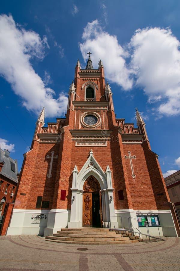 Ecclesia de romano-Catholica en Ukraine Ecclesia Kathedralis ?glise de Roman Catholic Cath?drale Immeuble de brique rouge, ciel b photographie stock libre de droits