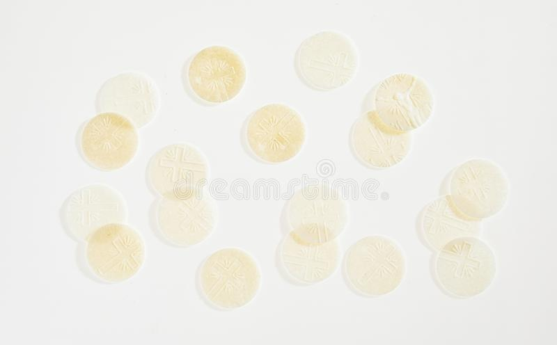 Ecclesiastical background of sacramental Hosties. Symbolising the resurrected body of Christ for use in the Holy Communion service scattered on white stock image