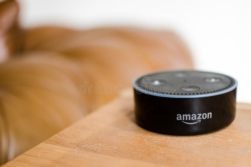 Echo dot version 2 in living room. Amazon echo dot, the machine learning artificial intelligence based Alexa on a table in living room with a brown sofa on stock image