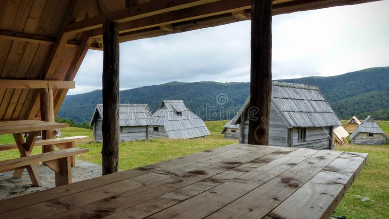 Echo village with wood houses with in the foreground a wood table and benches, Montenegro. Travel destination. Summertime and holidaytime. Cloudy sky. White stock photography