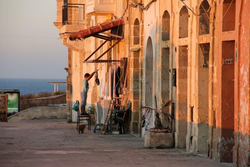 Echt aan overzeese van Malta kant tijdens oranje zonsondergang - jongen het hangen kleedt het drogen, twee wasmachines en gignger stock afbeeldingen