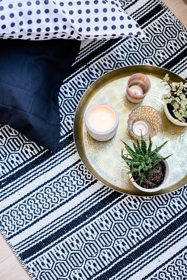 Echt flat binnenlands decor, aromatisch kaarsen en installaties op uitstekend dienblad met hoofdkussens en tapijt op de vloer stock fotografie