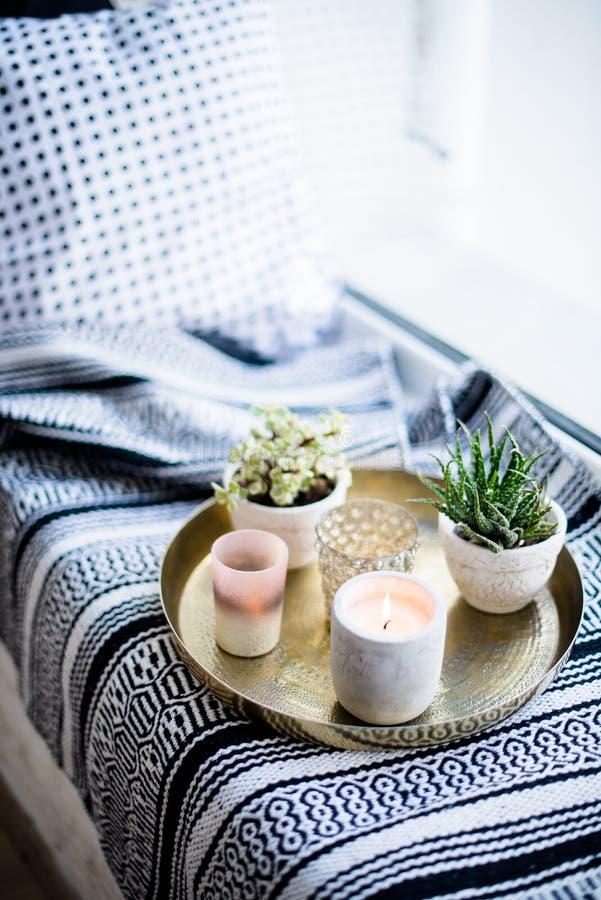 Echt flat binnenlands decor, aromatische kaarsen en installaties op uitstekend dienblad met hoofdkussens en deken op witte venste stock foto