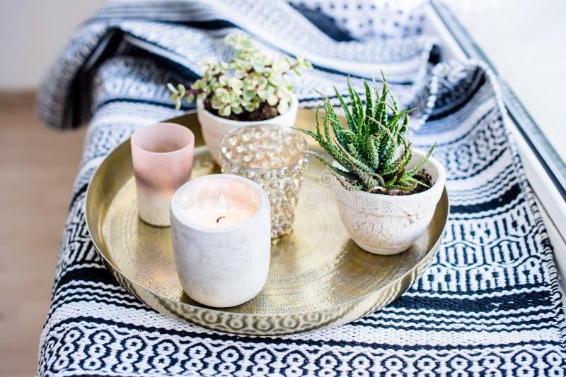 Echt flat binnenlands decor, aromatische kaarsen en installaties op uitstekend dienblad met hoofdkussens en deken op witte venste stock afbeelding
