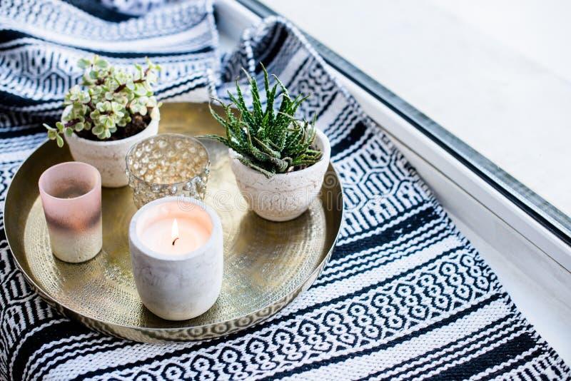 Echt flat binnenlands decor, aromatische kaarsen en installaties op uitstekend dienblad met hoofdkussens en deken op witte venste royalty-vrije stock fotografie