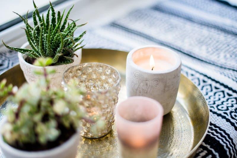 Echt flat binnenlands decor, aromatische kaarsen en installaties op uitstekend dienblad met hoofdkussens en deken op witte venste stock afbeeldingen