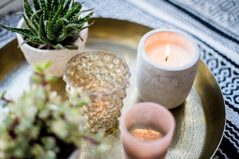 Echt flat binnenlands decor, aromatische kaarsen en installaties op uitstekend dienblad met hoofdkussens en deken op witte venste stock fotografie
