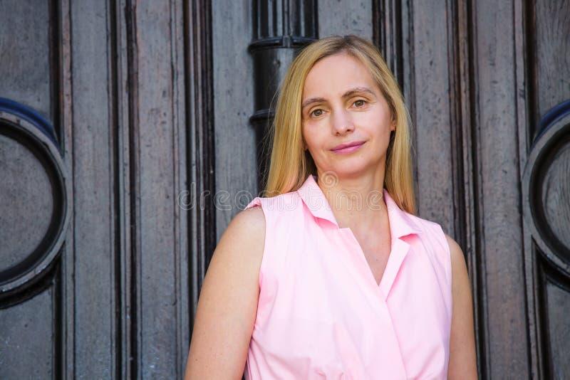 Echt gelukkig van de de aardzomer van de het blonde middenleeftijd van de portretvrouw lang het haarzonlicht vijftig plus roze 50 stock afbeelding