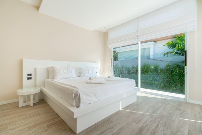 Echt Luxe Binnenlands ontwerp in slaapkamer van poolvilla met comfortabel koningsbed met hoog opgeheven plafondhuis, huis, de bou royalty-vrije stock fotografie
