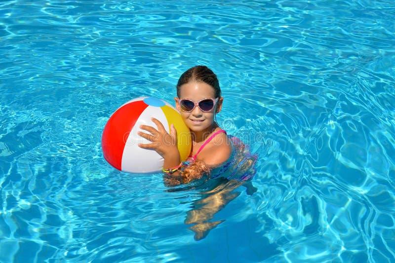 Echt schattig meisje ontspannend in zwembad stock fotografie