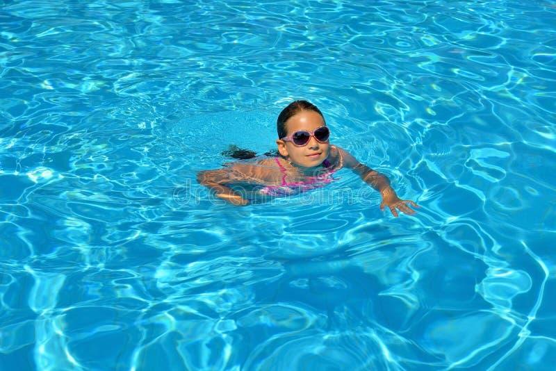 Echt schattig meisje ontspannend in zwembad royalty-vrije stock fotografie