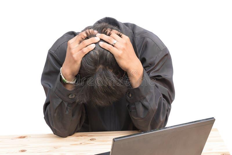 Echte etiketteringsproblemen een jonge mens zit bij zijn Bureau en houdt zijn handen op zijn hoofd stock foto