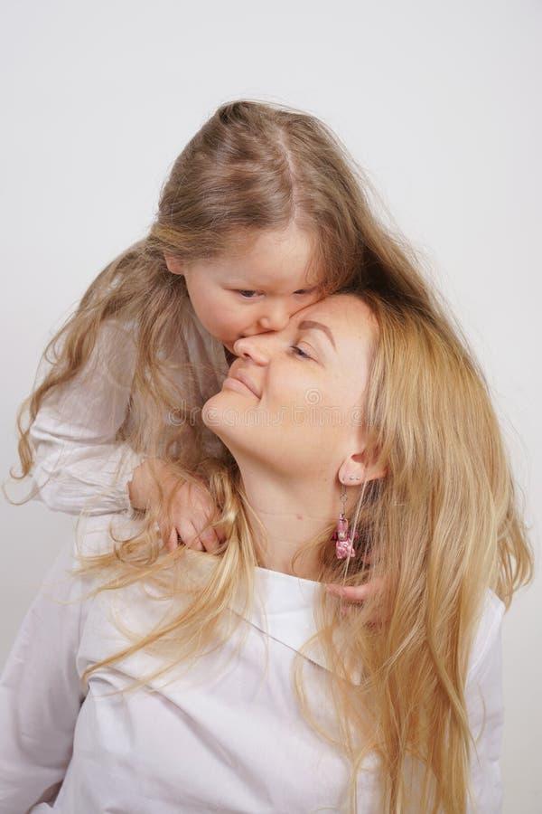 Echte familie van Kaukasische moeder en dochter in witte overhemden op de studioachtergrond royalty-vrije stock foto's