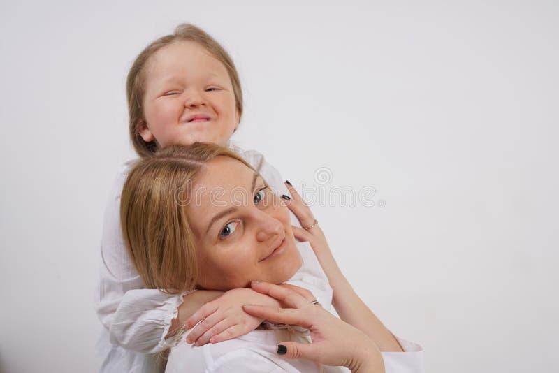 Echte familie van Kaukasische moeder en dochter in witte overhemden op de studioachtergrond stock foto