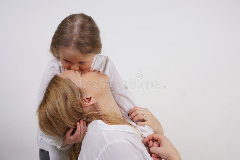 Echte familie van Kaukasische moeder en dochter in witte overhemden op de studioachtergrond royalty-vrije stock fotografie