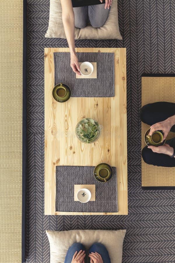Echte foto van drie mensen die het houten lijst drinken rondhangen royalty-vrije stock fotografie