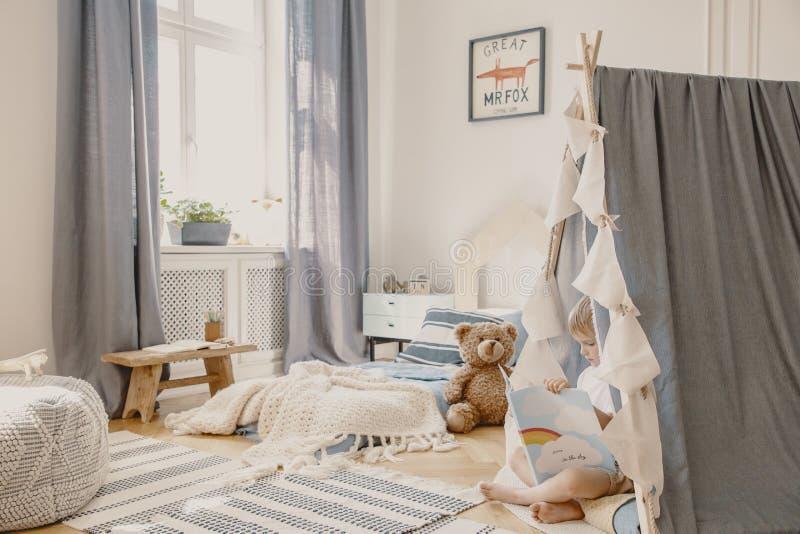 Echte foto van een blauw binnenland van de jong geitjeruimte met matras, gordijnen, teddybeer en tent waar een jongen een boek le stock afbeelding
