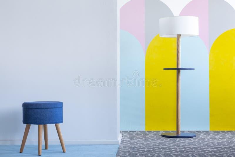 Echte foto van een blauwe kruk en een moderne lamp in het heldere leven ro royalty-vrije stock fotografie