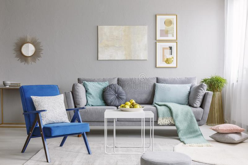 Echte foto van een blauwe leunstoel die naast een witte lijst zich binnen bevinden stock fotografie