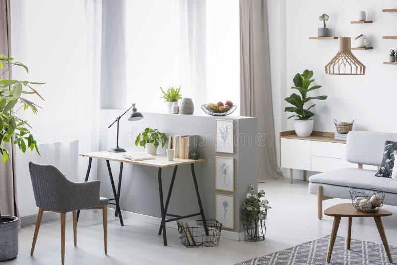 Echte foto van een helder binnenland van het huisbureau met een bureau, een leunstoel en installaties royalty-vrije stock afbeeldingen