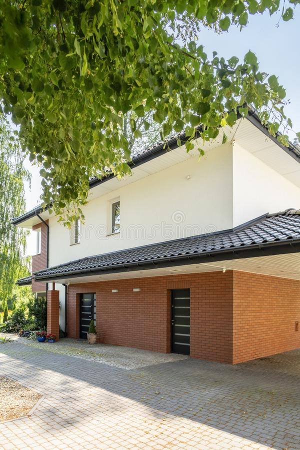 Echte foto van een modern huis met een voorwerf en een boom royalty-vrije stock foto