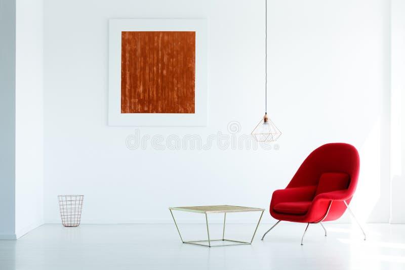 Echte foto van een rode leunstoel die zich naast een metaallijst bevinden in w royalty-vrije stock afbeeldingen