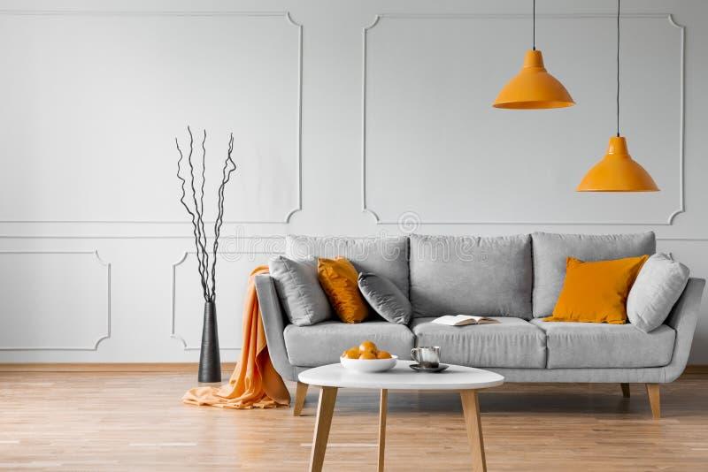 Echte foto van eenvoudig woonkamerbinnenland met oranje lampen, hoofdkussens en grijze bank stock afbeelding